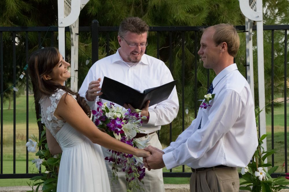 Bride and groom laugh at each other while their officiant reads their wedding vows during their simple backyard wedding in Menifee California