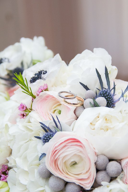 silver and gold Jewish wedding bands rest on a bouquet of pink and white roses and other beautiful flowers.