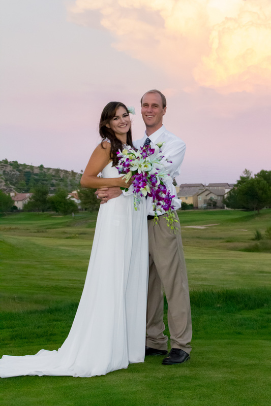 Bride and Groom pose for their wedding photo on a golf course in Menifee California. The sky is filled with pink purple and orange sunset clouds. The bride is holding a bouquet of purple orchids and white lilies and wearing a soft casual flowing wedding dress.
