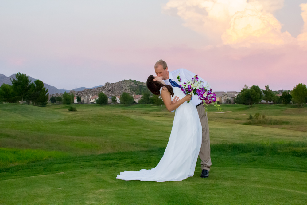 Bride and Groom kiss on a golf course with lush green grass and sunset pink orange and purple clouds behind them in menifee california. They are wearing casual wedding dress and suit and the bride is holding a bouquet of purple orchids and white lilies.