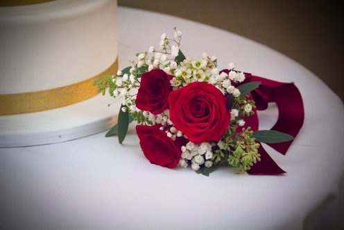 Rose corsage next to wedding cake