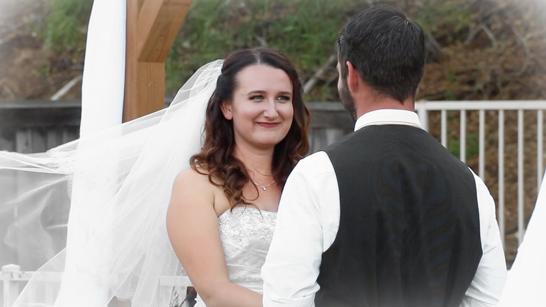 Bride smiles lovingly at groom during their backyard wedding ceremony.