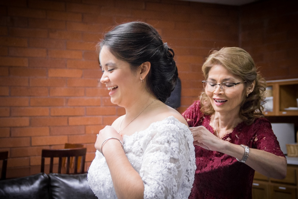 Bride laughs as mother helps her dress for her red and white themed wedding