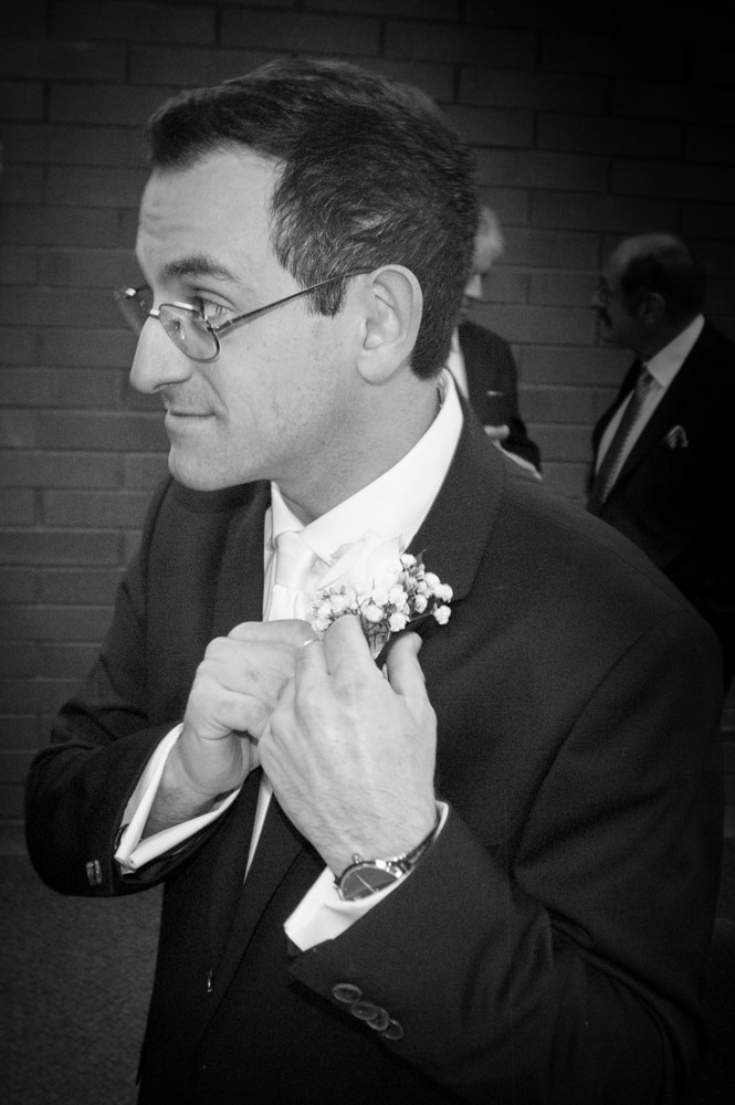 groom puts on boutonnière on wedding day