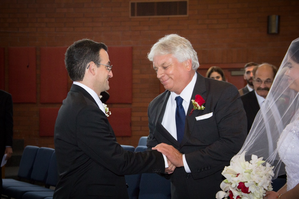 Father shakes hands with groom