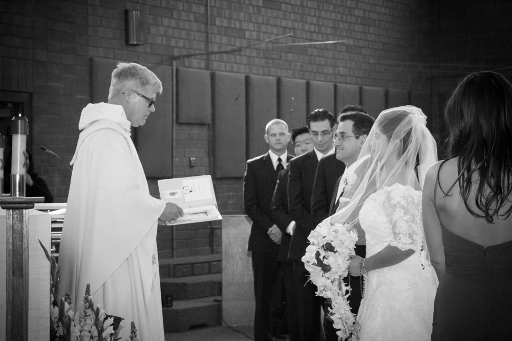 Priest speaks to bride and groom during wedding mass