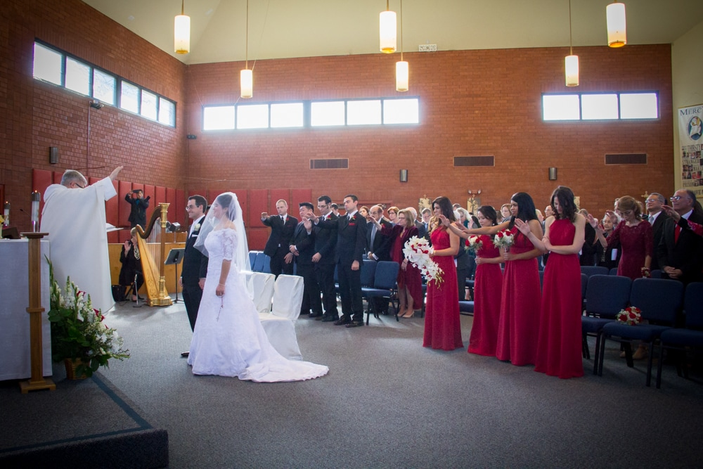 Wedding guests bless the couple during mass.