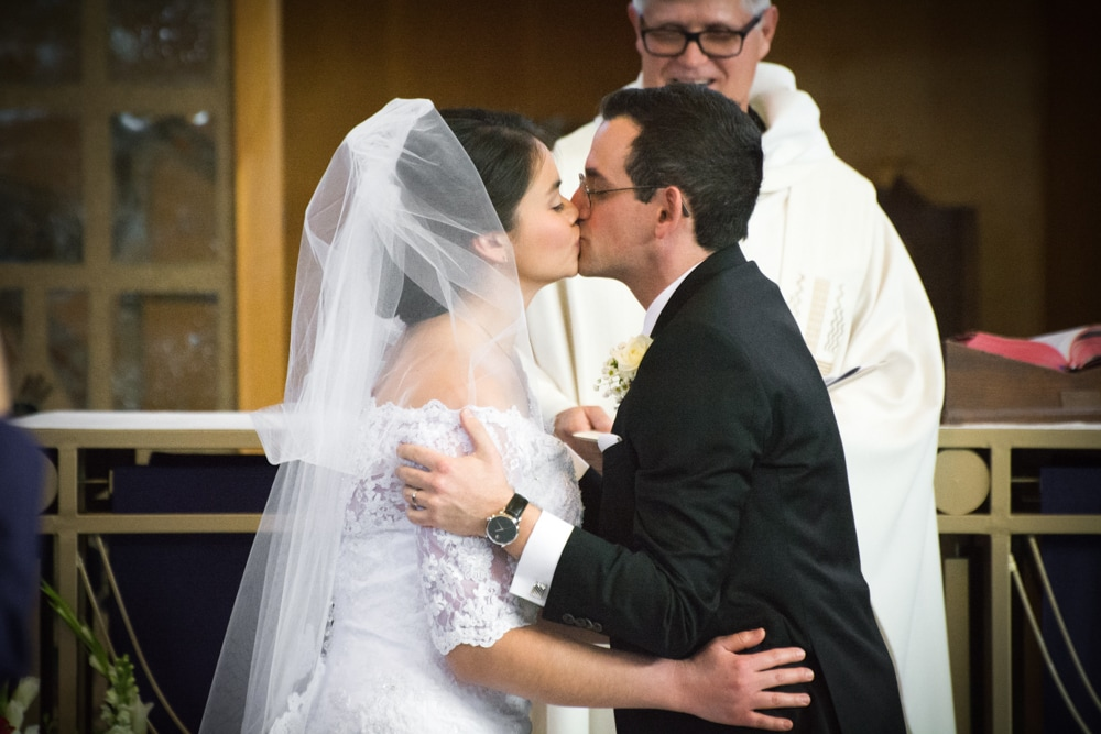 Bride and groom share first kiss as husband and wife during Catholic wedding ceremony.