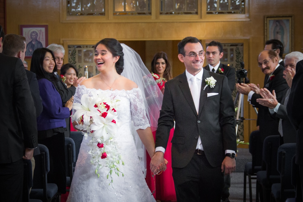 Bride and Groom happily exit their wedding ceremony with guests cheering and applauding