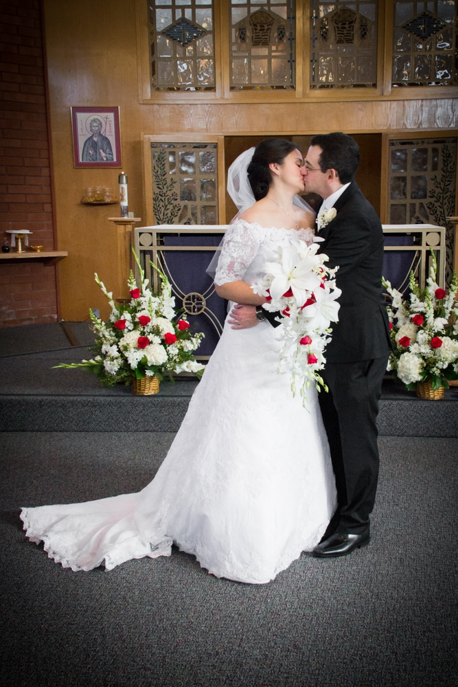 Wedding portrait of bride and groom kissing in Catholic Church