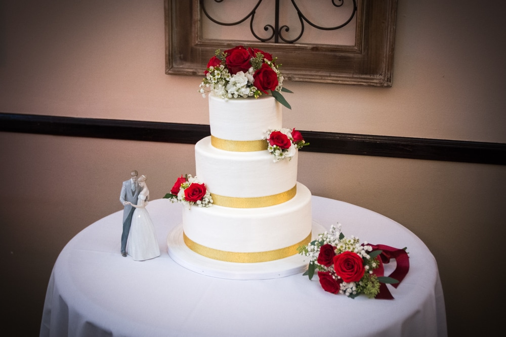 Classic White Wedding Cake with Gold Trim and red roses