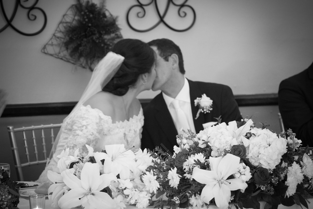 Bride and Groom kiss in soft focus behind head table flowers