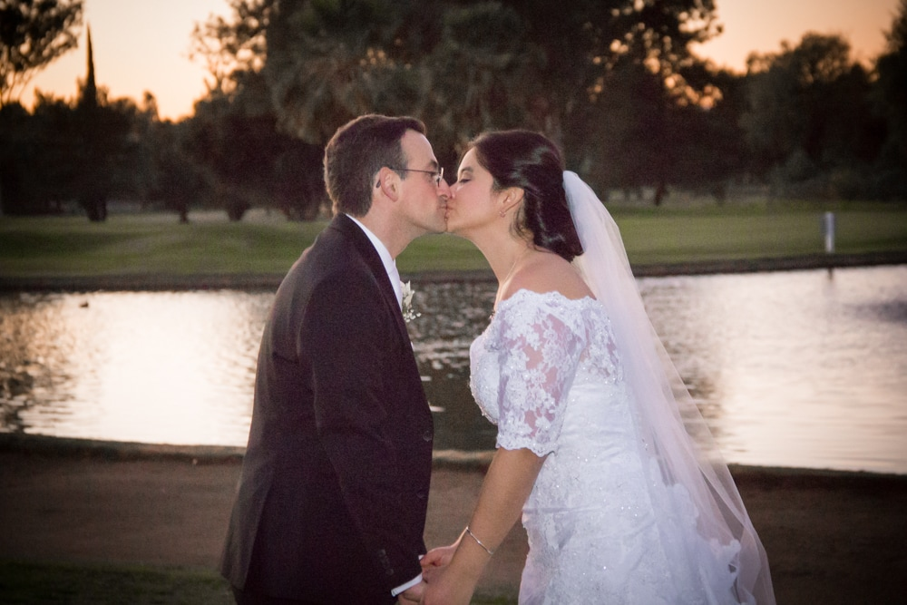 Bride and groom kiss in front of lake on Mother-Son dance at Canyon Crest Country Club golf course