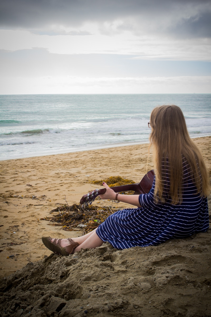 High school senior girl looks out at the ocean in Newport Beach, CA