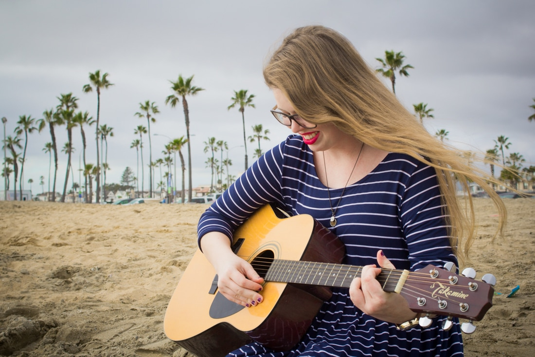 high school senior plays guitar with storm clouds behind her at balboa pier