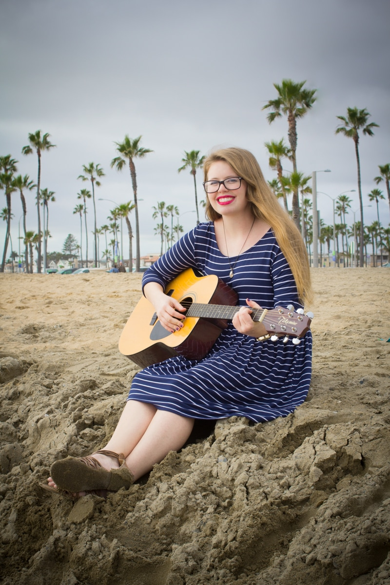 Smiling girl with guitar during senior photography session at Balboa Pier