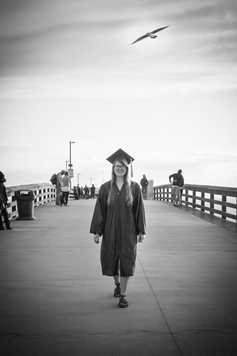 Black and white photo of graduate walking down balboa pier