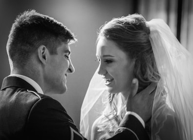 groom brings his bride in closer for a kiss