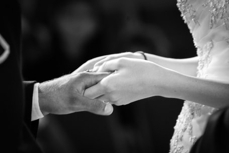 black and white photo of couple's clasped hands during ring ceremony