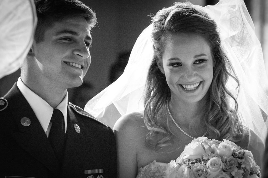black and white photo of a bride and groom laughing during their wedding ceremony
