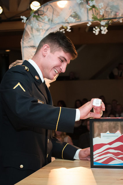 military groom laughs during patriotic themed wedding sand ceremony