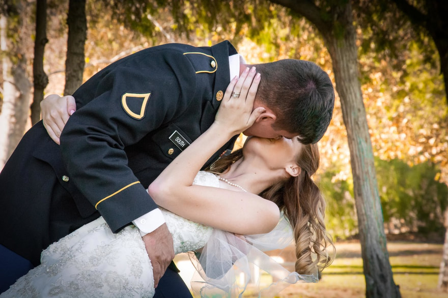 military coupel kiss during wedding portraits with fall colors glowing behind them