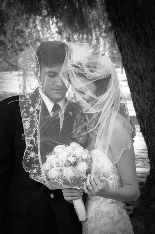 bride and groom under veil at Neil Snipes' park in Norco CA