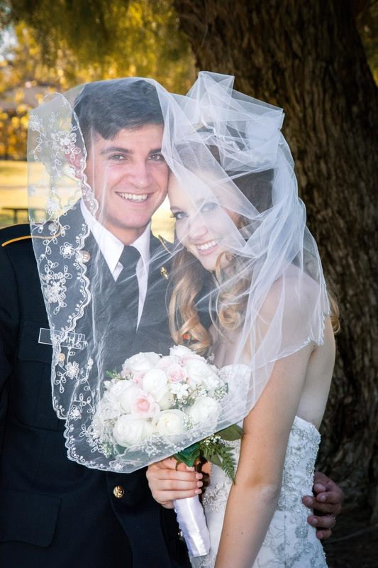 military groom and bride smile under veil during portrait session