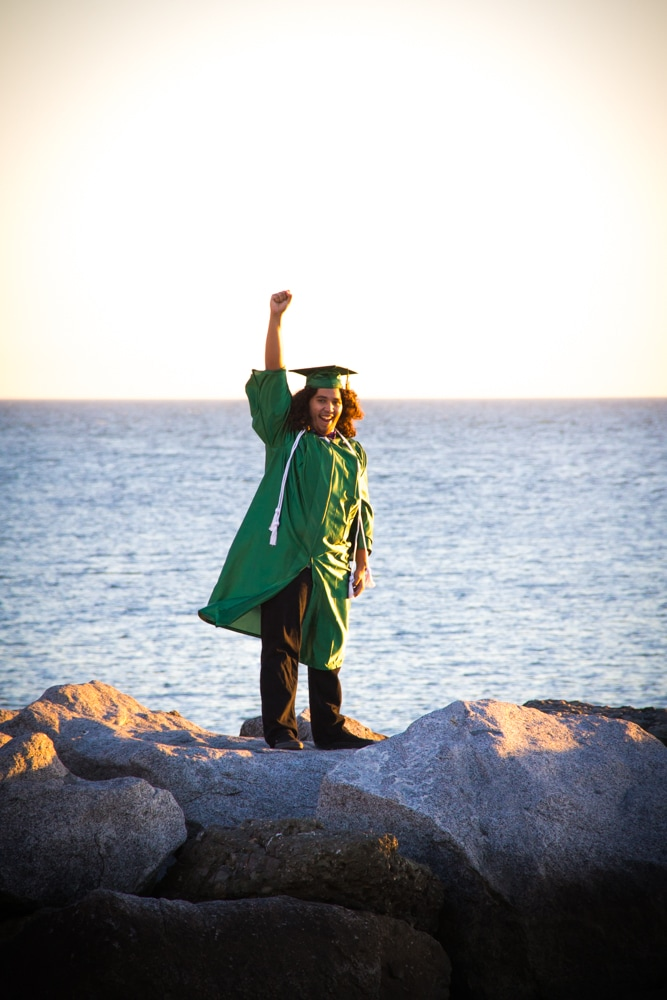 Graduating senior guy cheers on the jetty at Corona Del Mar Beach